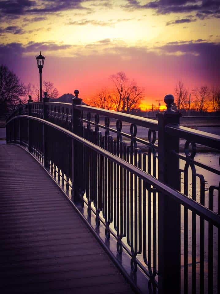 Bridge over park pond at sunset